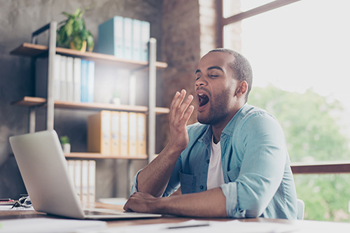 Person yawning who may be suffering from sleep apnea
