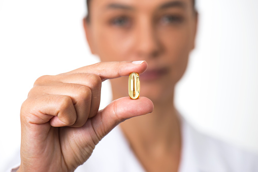 Woman Holding Fish Oil Pill