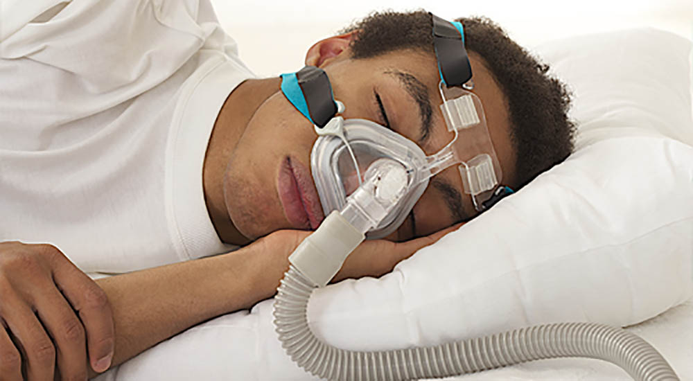 Man wearing CPAP mask to assist with sleeping