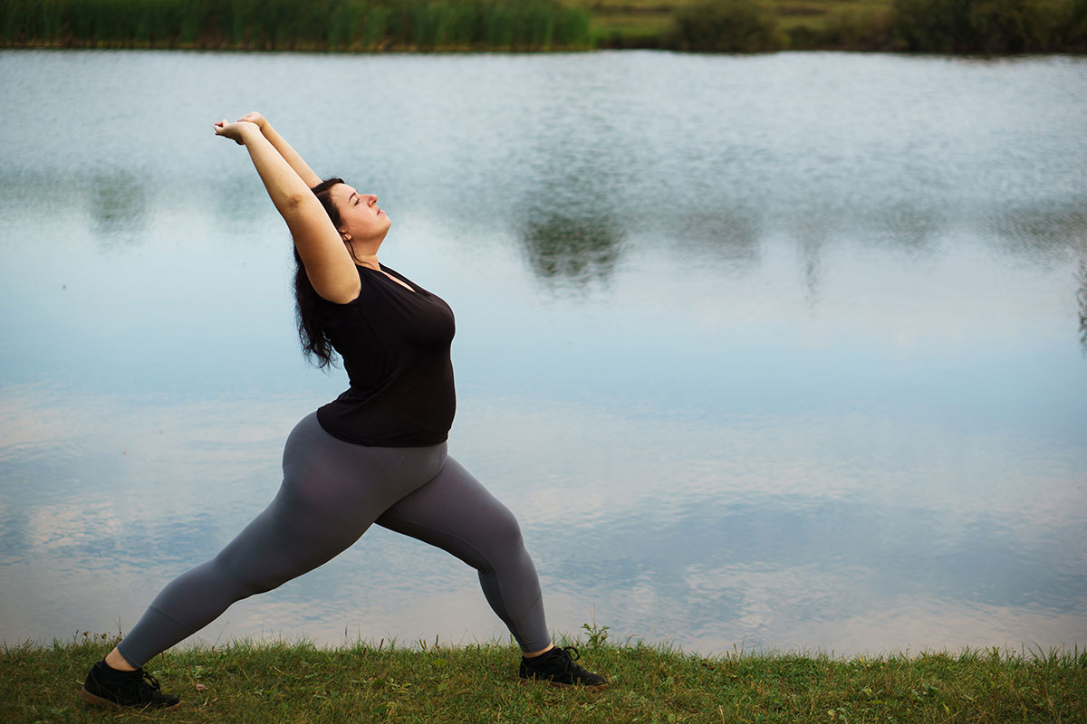 Woman stretching at lake as part of her bariatric surgery recovery